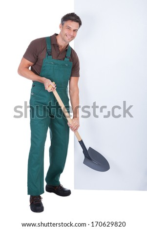 Portrait Of Cheerful Male Gardener With Shovel Presenting Blank Placard