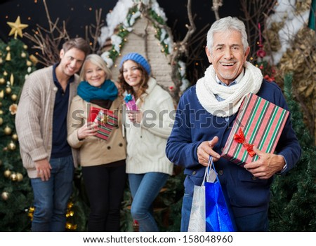 Portrait of cheerful man holding Christmas presents and shopping bags with family standing in background at store - stock photo