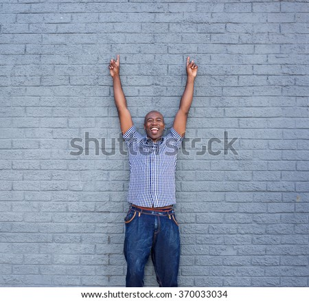 Portrait of cheerful man standing with his hands raised against a gray wall  - stock photo