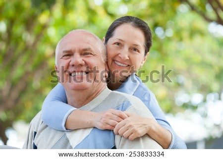 Portrait of cheerful mature couple together in autumn park - stock photo