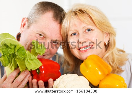 Portrait of cheerful mature man and woman smiling together at a kitchen - stock photo