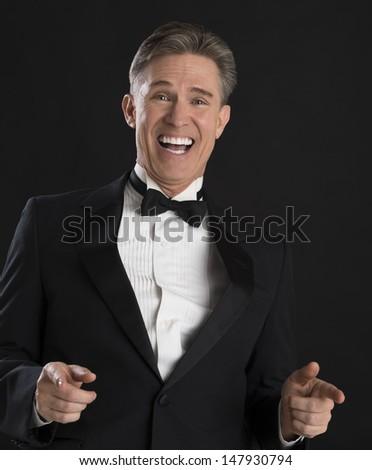 Portrait of cheerful mature man in tuxedo gesturing against black background - stock photo