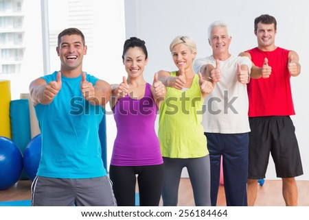 Portrait of cheerful men and women gesturing thumbs up at gym - stock photo