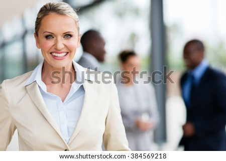 portrait of cheerful mid age business executive in office - stock photo
