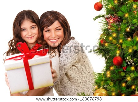 Portrait of cheerful mother and daughter on Xmas eve having fun, receive gifts, isolated on white background, beautiful Christmas tree, happy holidays concept - stock photo