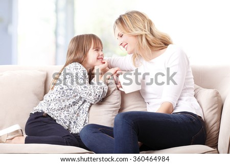 Portrait of cheerful mother and daughter sitting at home on sofa while relaxing and laughing together.  - stock photo