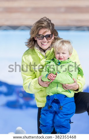 Portrait of cheerful mother in sunglasses with little blond boy on a ski resort - stock photo