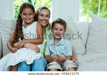 Portrait of cheerful mother with daughter and son on sofa at home - stock photo