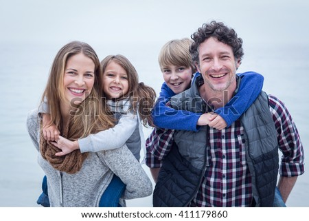 Portrait of cheerful parents carrying children at beach - stock photo