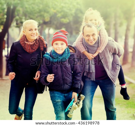 Portrait of cheerful parents with two children spending time together outdoors - stock photo