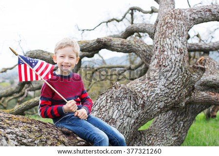 portrait of cheerful patriotic boy holding american flag and celebrating 4th of july - stock photo