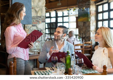 Portrait of cheerful people having dinner and respectful waiter - stock photo