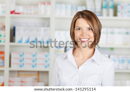 Portrait of cheerful pharmacist standing inside the drugstore - stock photo