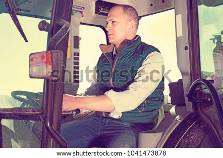 Portrait of cheerful positive  handsome man working on farm tractor in vineyard