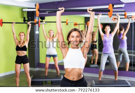 Portrait of cheerful positive  women exercising with barbell in fitness club