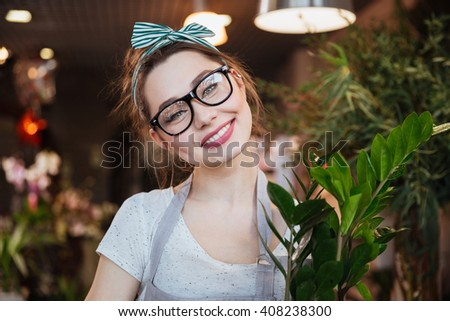 Portrait of cheerful pretty young woman florist in glasses in flower shop - stock photo