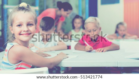 Portrait of cheerful pupil girl studying in school class