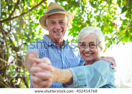 Portrait of cheerful retired couple dancing outdoors - stock photo