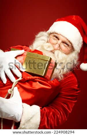 Portrait of cheerful Santa Claus holding huge sack full of gifts - stock photo