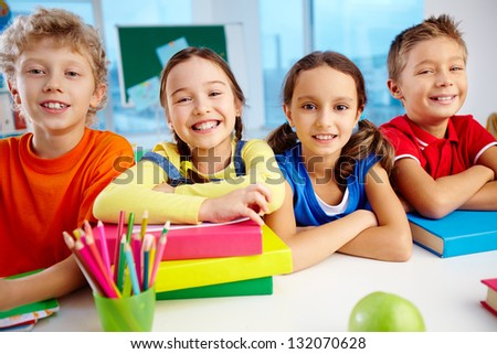 Portrait of cheerful school children flashing toothy smiles - stock photo