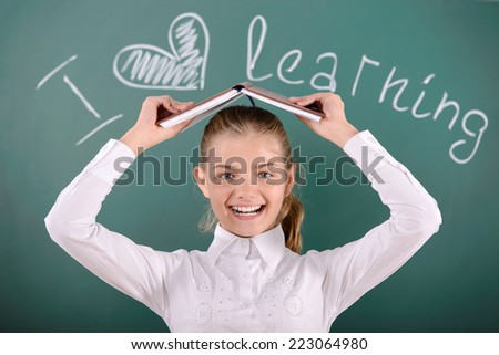 Portrait of cheerful school girl standing near blackboard