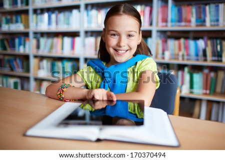 Portrait of cheerful schoolgirl looking at camera while sitting in library - stock photo