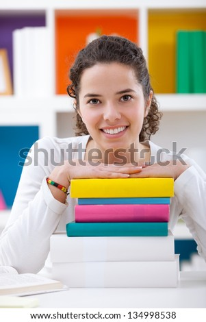 portrait of cheerful schoolgirl with colorful books - stock photo
