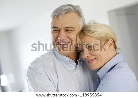 Portrait of cheerful senior couple at home - stock photo