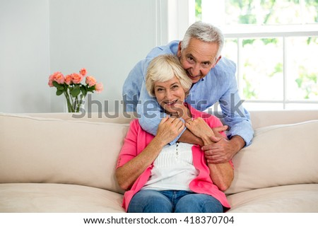 Portrait of cheerful senior couple hugging at sofa - stock photo