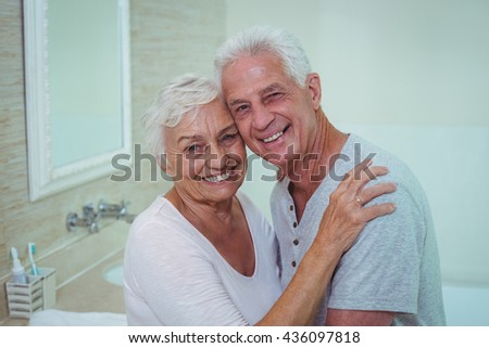 Portrait of cheerful senior couple standing in bathroom - stock photo