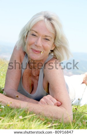 Portrait of cheerful senior woman in natural landscape