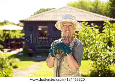 Portrait of cheerful senior woman with gardening tools outdoors. Older woman standing with shovel in her backyard garden - stock photo