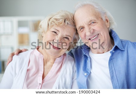 Portrait of cheerful seniors looking at camera with smiles - stock photo