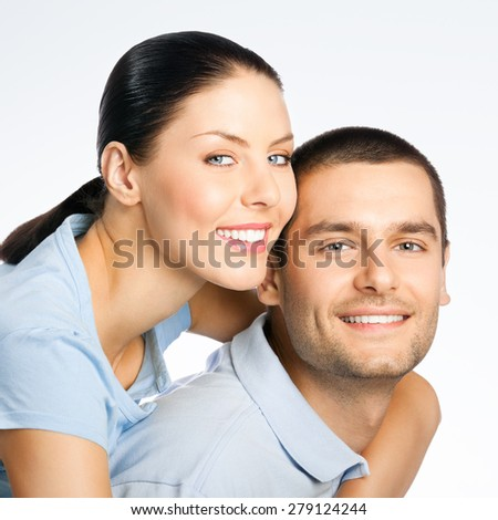 Portrait of cheerful smiling amorous young couple, over grey background - stock photo
