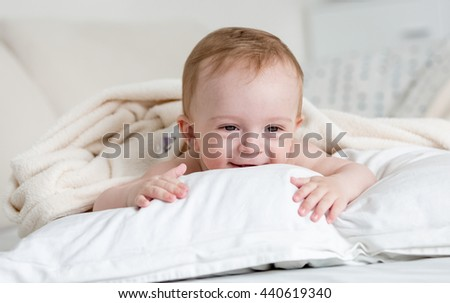 Portrait of cheerful smiling baby boy relaxing on big white pillow on bed - stock photo