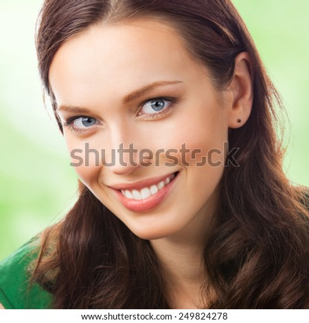 Portrait of cheerful smiling beautiful young woman, outdoor - stock photo