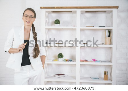 Portrait of cheerful smiling business lady in modern office interior