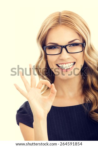 Portrait of cheerful smiling businesswoman in glasses, showing okay gesture - stock photo