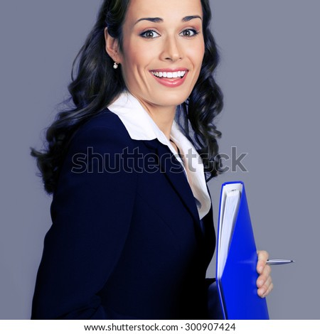 Portrait of cheerful smiling businesswoman in glasses, with blue folder, posing at studio, over violet background - stock photo