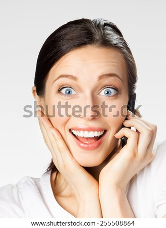 Portrait of cheerful smiling businesswoman with cell phone, on grey - stock photo