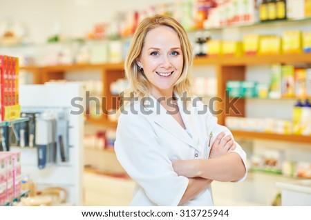 portrait of cheerful smiling female pharmacist chemist woman in pharmacy drugstore - stock photo