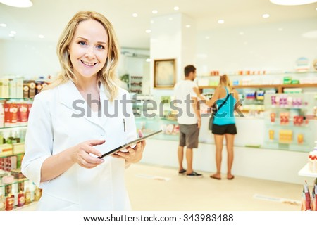 portrait of cheerful smiling female pharmacist working with tablet computer in pharmacy drugstore - stock photo