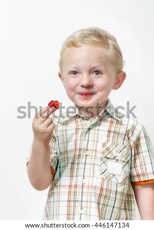 Portrait of cheerful smiling little  boy eating red strawberry on a white background - stock photo