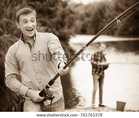 portrait of cheerful smiling man casting line for fishing on river