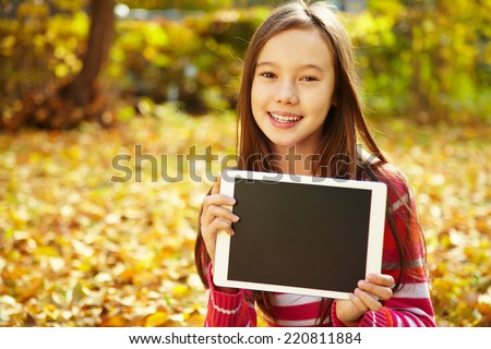 portrait of cheerful smiling teenage girl with tablet computer outdoor - stock photo