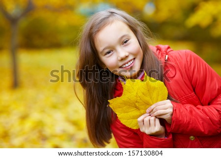 portrait of cheerful smiling teenage girl with yellow leaves in autumn