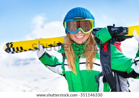 Portrait of cheerful smiling woman with ski equipment in snowy mountains, having fun outdoors in winter time, happy healthy lifestyle - stock photo