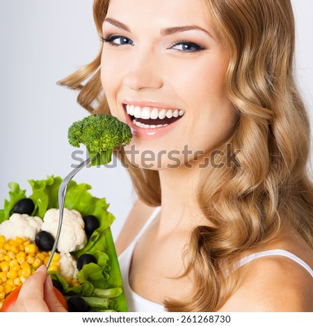 Portrait of cheerful smiling young blond woman eating vegetarian salad, against grey background. Healthy eating and dieting concept. - stock photo