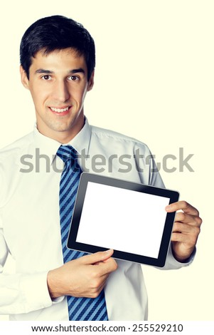 Portrait of cheerful smiling young businessman showing no-name blank taplet pc with copyspace area for text or slogan - stock photo