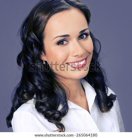Portrait of cheerful smiling young businesswoman, over violet background - stock photo